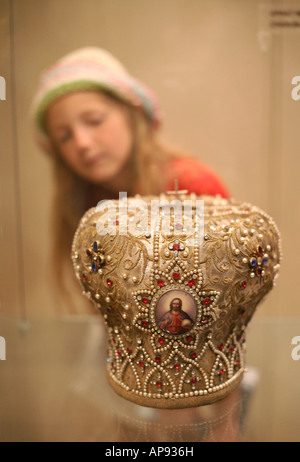 Young Russian pilgrim looking at the miter in the Treasury Museum of Cetinje Monastery, Montenegro - Stock Photo