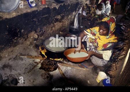 Woman cooking rice inside her hut on Lamu Island Kenya - Stock Photo