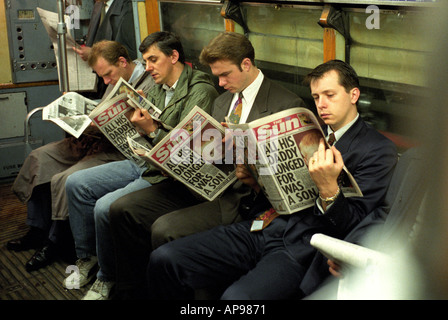 Men reading the sun newspaper on the tube train in London - Stock Photo