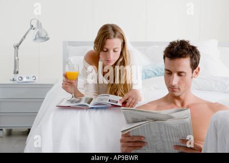 Couple reading in bedroom - Stock Photo