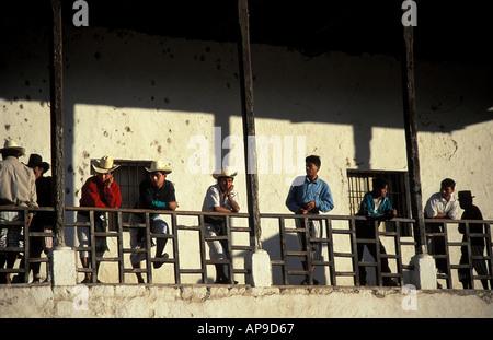 Tzutujil Maya men gather in the church corridor overlooking the plaza SantiagoAtitlan Guatemala - Stock Photo