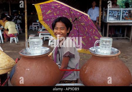 Friendly drink vendor under a parasol umbrella Nat festival near Mandalay Burma Myanmar Taungboyone Nat Festival - Stock Photo