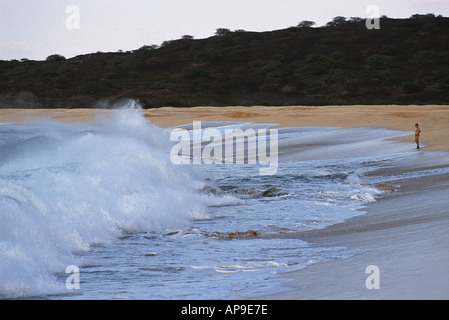 man on beach looking giant waves - Stock Photo