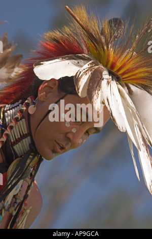 A Native American young man, wearing traditional headdress, dances at regional powwow - Stock Photo