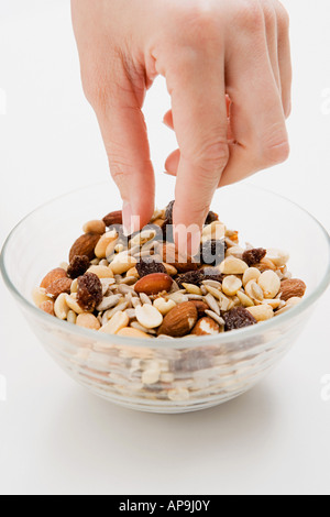 Young woman picking at a bowl of nuts - Stock Photo