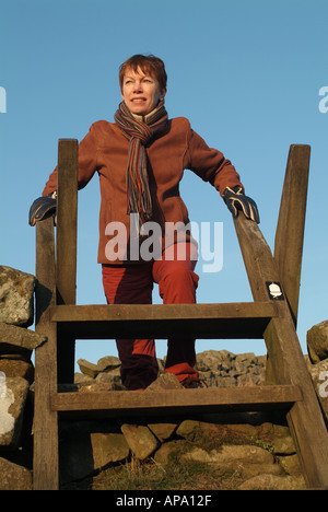 Woman 40 to 50's Climbing a stile on the Pennine Way near Crag Lough, Northumberland, England, UK. - Stock Photo