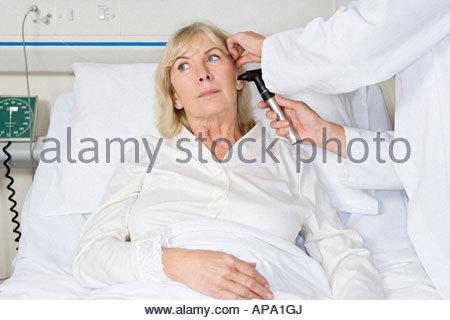 Doctor examining womans ear - Stock Photo