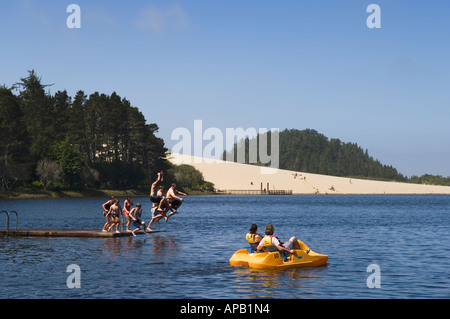 Couple in paddleboat and group of teenagers jumping off float Cleawox Lake Honeyman State Park Oregon Coast - Stock Photo