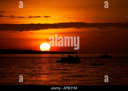 Local fishermen sail out in the early evening to fish the waters around Manado North Sulawesi Indonesia - Stock Photo