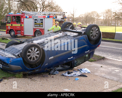 Overturned car and fire engine at scene of road accident , West Midlands , UK - Stock Photo