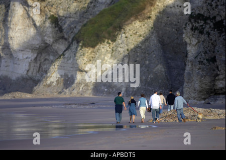 seven person extended family group walking along the beach beneath cliffs white rocks beach portrush - Stock Photo