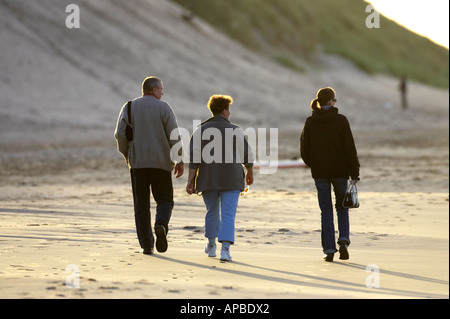 mother father and older daughter family walking along the beach white rocks beach portrush county antrim northern - Stock Photo