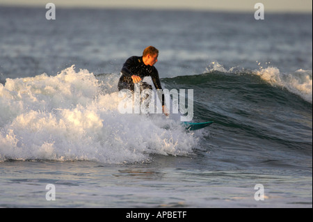 male surfer in wetsuit surfs on waves off white rocks beach portrush county antrim northern ireland - Stock Photo