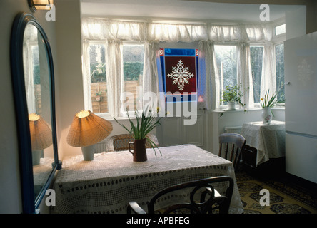 Lamp On Table In Small Dining Room Extension With Stained Glass Panel Door