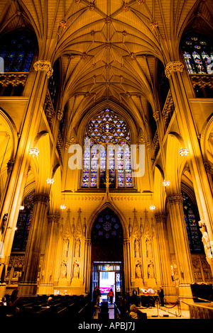 Inside St. Patrick's Cathedral in Manhattan, a symmetric capture featuring the entrance, stained-glass window above - Stock Photo