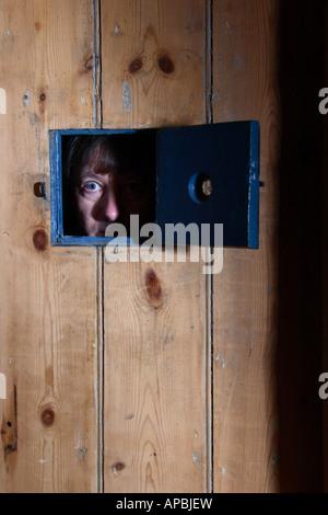 Prisoner looking out of jail door window. - Stock Photo