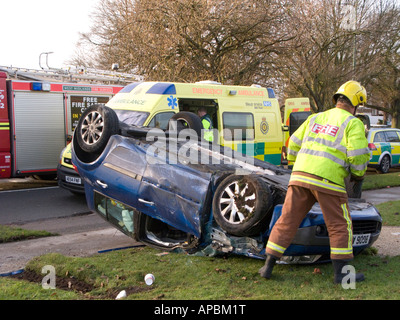 Fireman checks overturned car at road accident scene - Stock Photo