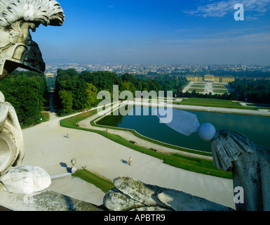 View from The Folly framed by ornate stone figure down to ornamental lake The Schonbrunn Palace Gardens Vienna Austria - Stock Photo