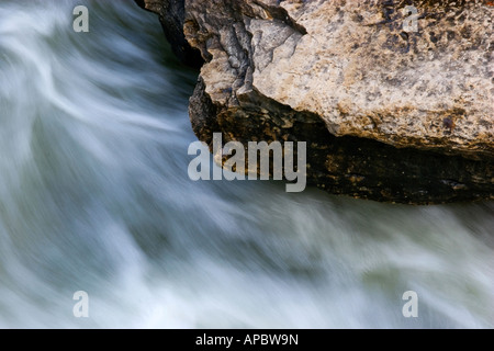 Water rushes past an outcropping below the water fall at the Tanyard Creek Trail in Bella Vista, Ark. - Stock Photo