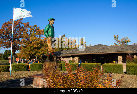 Mulligan, a wooden statue, looks out over the HIghlands Club House at Highlands Golf Course in Bella Vista, Ark. - Stock Photo