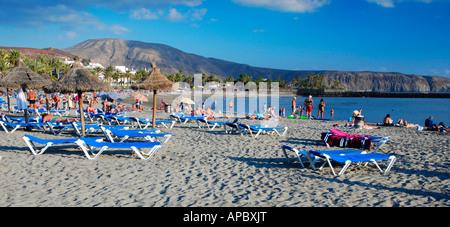 Beach life at Playa de Camisón beach in Playa de las Américas/Los Cristianos on Tenerife island, Spain - Stock Photo