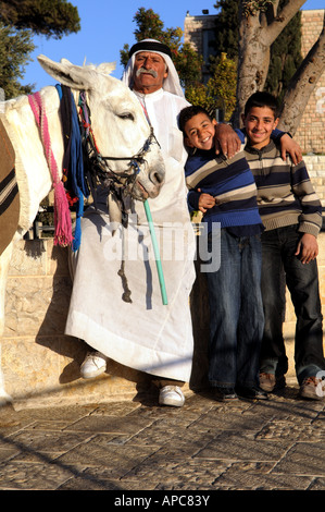 A family portrait- Standing with their donkey On the beautiful Mt of olives promenade in Jerusalem. - Stock Photo