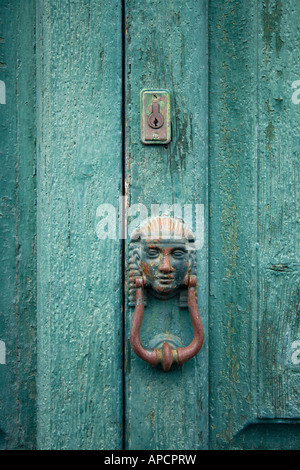 antic doorknocker in human face shape and lock on green weathered wooden door - Stock Photo