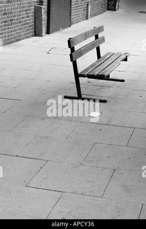 black and white image off a bench with nobody in sight in a walkway area off a town centre - Stock Photo