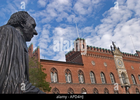 The statue of H C Andersen overlooking the gothic styled town hall built in 1883 Flakhaven Odense Denmark - Stock Photo