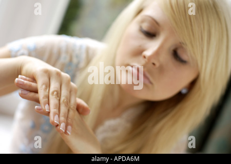 woman looking at her hands - Stock Photo