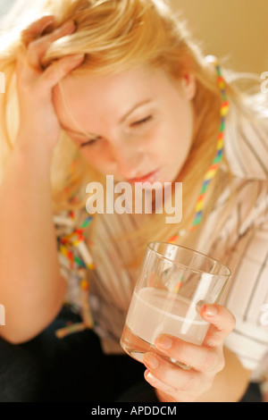 woman with streamers and hangover - Stock Photo