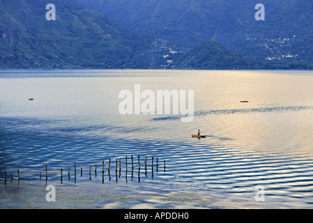 GUATEMALA LAKE ATITLAN Fishermen in traditional cayucos small wooden boats made of avocado wood - Stock Photo
