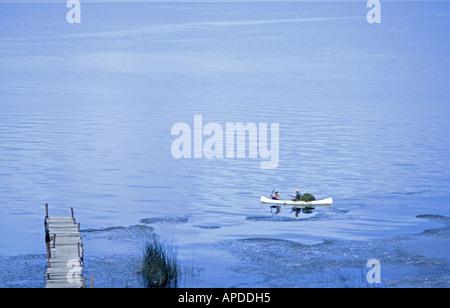 GUATEMALA LAKE ATITLAN Fishermen in a canoe collecting algae on Lake Atitlan Guatemala - Stock Photo