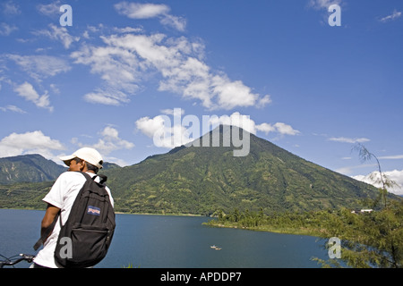 GUATEMALA LAKE ATITLAN Bicyclist stopped at overlook in Santiago Atitlan with San Pedro Volcano - Stock Photo