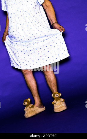 Senior woman wearing gown and bear slippers - Stock Photo