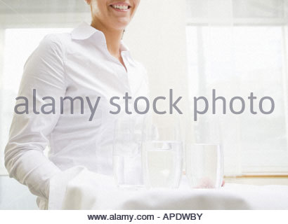 Waitress carrying glasses of water - Stock Photo