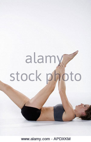 Woman in athletic gear stretching - Stock Photo
