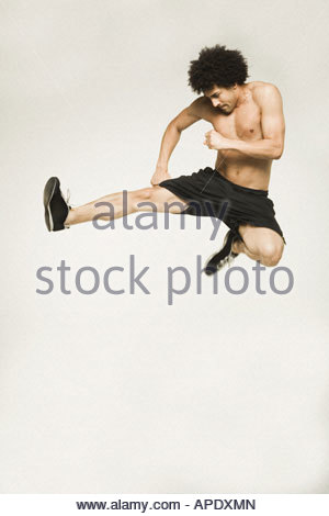 Bare-chested man jumping and kicking - Stock Photo