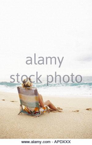 Woman sitting in beach chair - Stock Photo