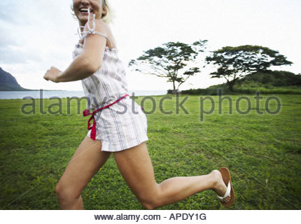 Young woman running through field - Stock Photo