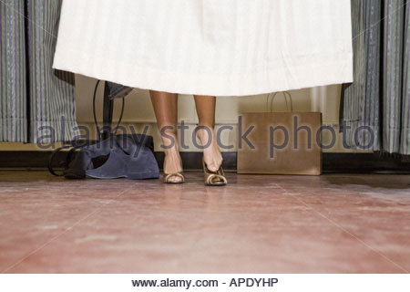 Woman behind fitting room curtain - Stock Photo
