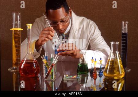 Chemist examines fluids in beakers - Stock Photo