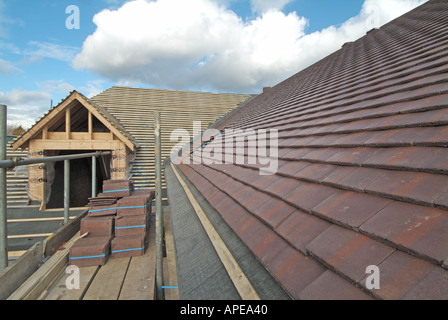 Detached house construction roof partly covered with Marley concrete plain roof tiles showing eaves felt batten - Stock Photo