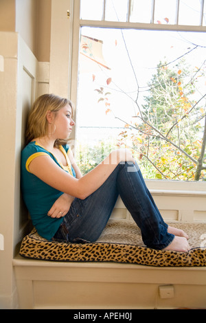 Teenaged girl looking out window - Stock Photo
