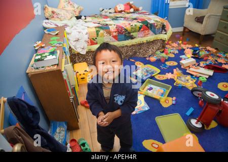 Asian boy in messy bedroom - Stock Photo