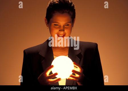 Woman gazes at glowing globe. - Stock Photo