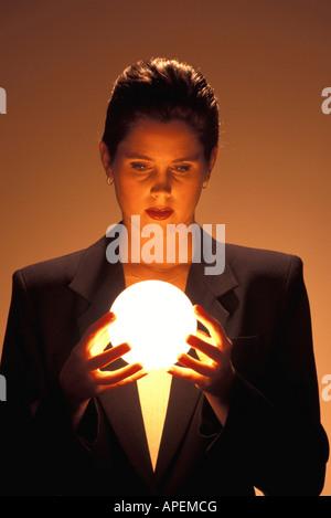 Woman gazes into blowing ball. - Stock Photo