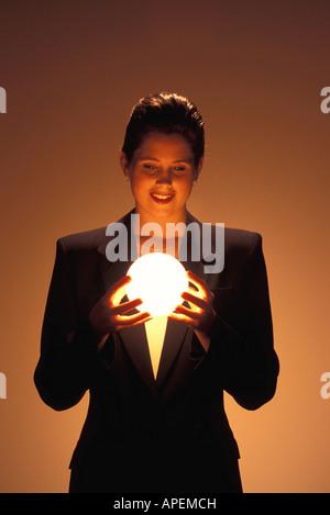 Woman gazes into glowing ball. - Stock Photo