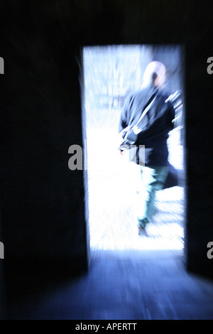 A man walking out from a door touching his toes to the doormat