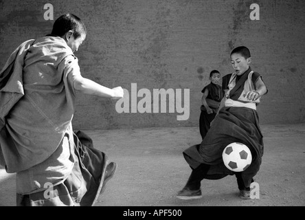 Yellow Hat Monks playing football in the Xiahe monastery Gansu Province Peoples Republic of China - Stock Photo